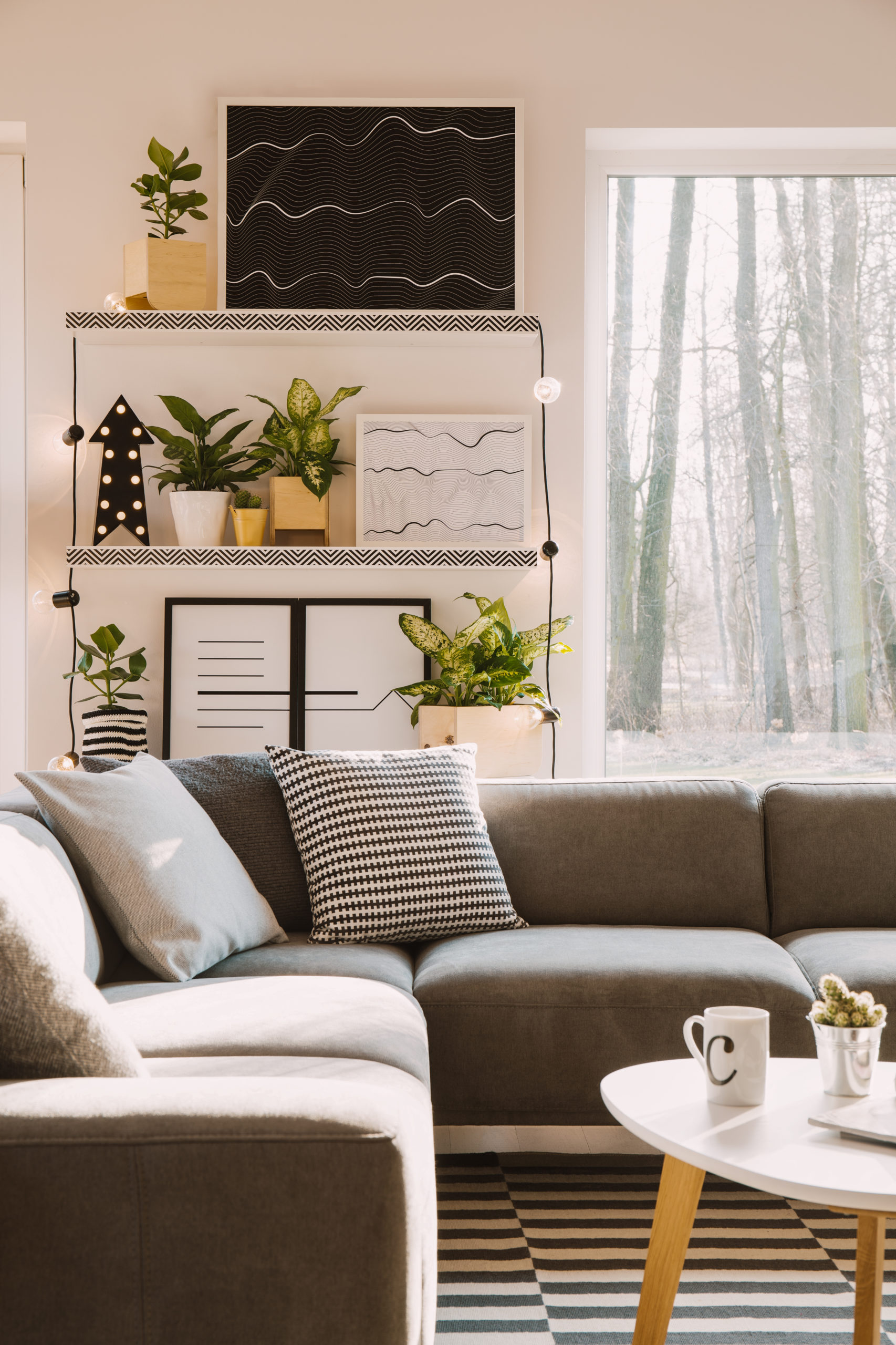 Pillows with pattern on grey corner couch standing in bright Nordic living room interior with posters, green plants, lamps and window