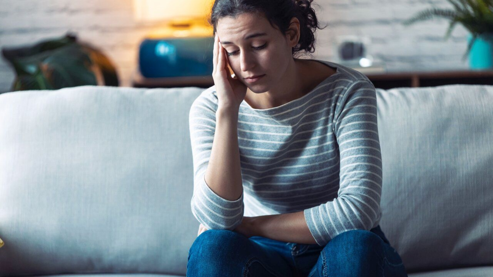 Shot of worried young woman thinking while sitting on sofa in the living room at home.